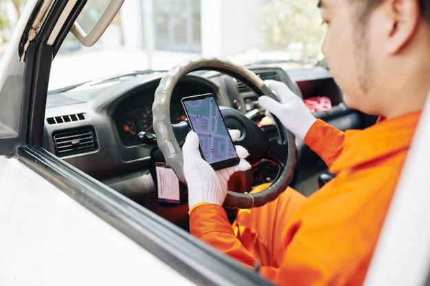 Zusteller überprüft karte auf smartphone