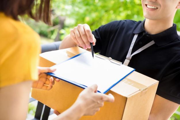 Zusteller zeigt auf das dokument, das zeigt, wo zu unterschreiben ist, während er paketbox an eine frau liefert