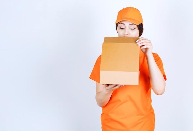 Zustellerin, die in das paket schaut