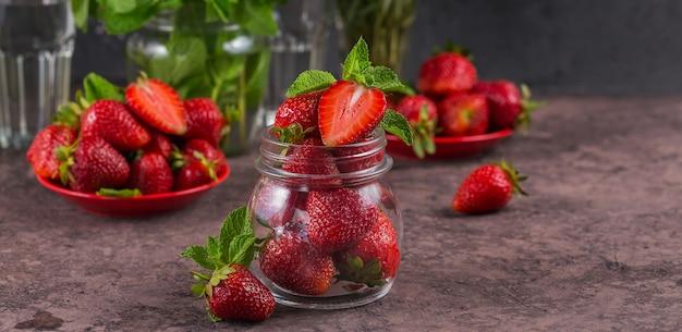 Zutat für hausgemachte erdbeermarmelade oder marmelade im glas mit reifen süßen beeren und minzblättern