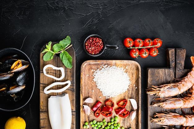 Zutat für spanische meeresfrüchte-paella mit garnelen und tintenfischen auf schwarzer betonoberfläche
