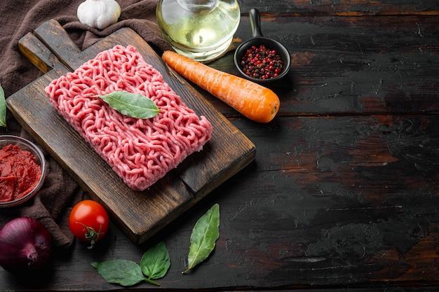 Zutaten der bolognese-sauce, hackfleisch-tomaten und kräuter, auf holzschneidebrett, auf altem dunklem holztisch