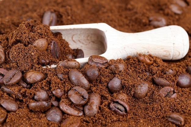 Zutaten, die verwendet werden können, um ein heißes, belebendes kaffeegetränk, nahaufnahme-kaffeebohnenpulver und ganze kaffeebohnen zuzubereiten, geröstete bohnen werden auf gemahlenen kaffee gelegt