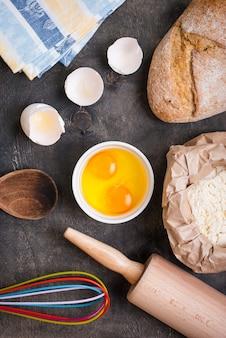 Zutaten für backen, eierschale, brot, mehl und nudelholz auf schwarzem tisch