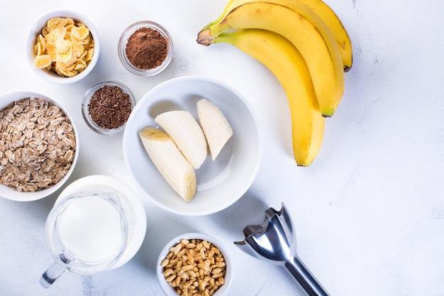 Zutaten für bananen-smoothie auf weißem grund. konzept für gesunde ernährung.