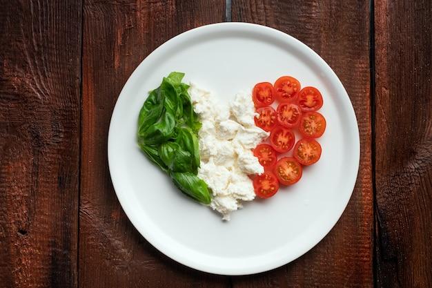 Zutaten für caprese-salat in form eines herzens. italienische flagge aus traditionellen lebensmitteln