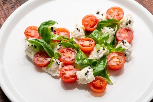 Zutaten für caprese-salat in form eines herzens. symbol der liebe zum italienischen essen