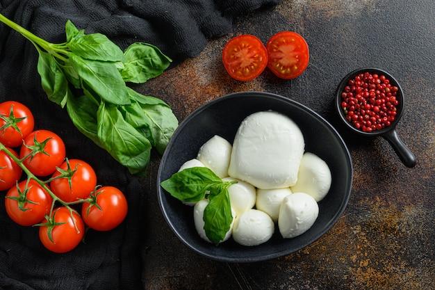 Zutaten für caprese-salat: mozzarella-bällchen mit tomaten und basilikum