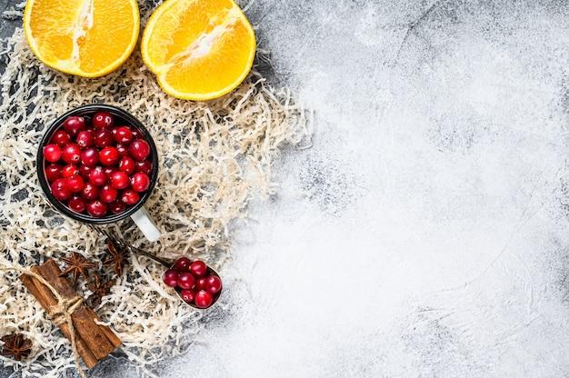 Zutaten für das backen von keksen im winter. lebkuchen, obstkuchen, getränke. preiselbeeren, orangen, zimt, gewürze. weihnachtsessen. grauer hintergrund. draufsicht. platz für text