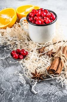 Zutaten für das backen von keksen im winter. lebkuchen, obstkuchen, getränke. preiselbeeren, orangen, zimt, gewürze. weihnachtsessen. grauer hintergrund. draufsicht