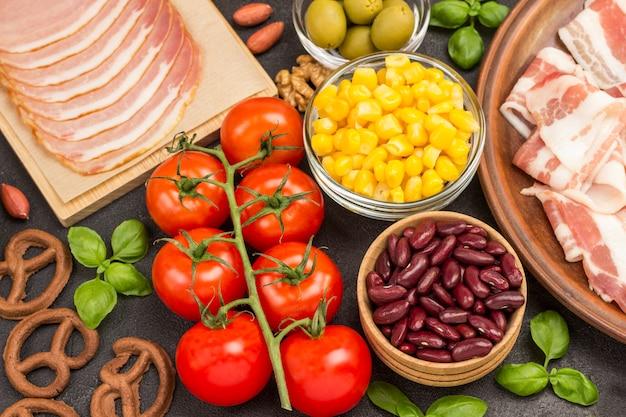 Zutaten für das frühstück: speck-mais-tomaten-basilikum.