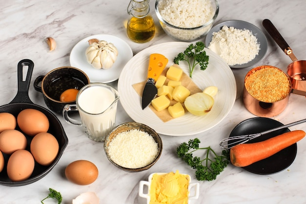Zutaten für das kochen von arancini auf weißem grauem marmorhintergrund. käse, reis, milch, ei, karotte, petersilie, butter, knoblauch, semmelbrösel und parmesan