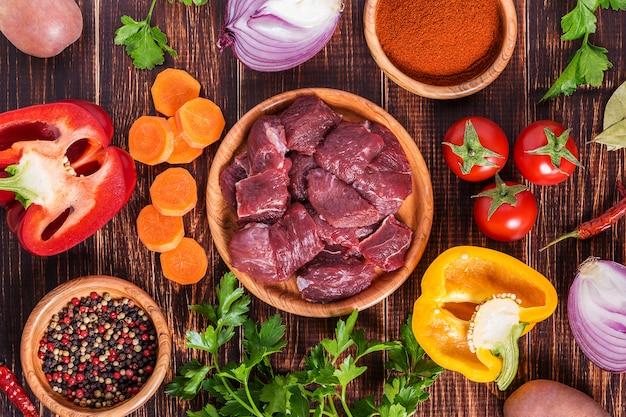Zutaten für das kochen von gulasch oder eintopf: rohes fleisch, kräuter, gewürze, gemüse auf dunklem holztisch.