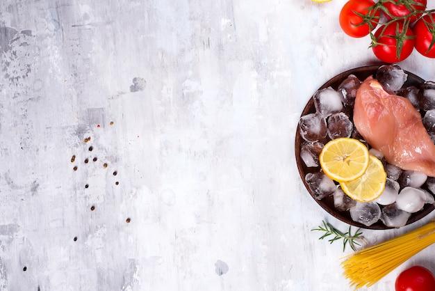 Zutaten für das kochen von nudeln mit hähnchen, tomaten, zitronenscheibe und eis.
