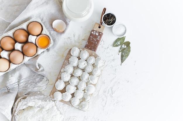 Zutaten für das modellieren von hausgemachten knödeln. eier, milch, mehl, salz, pfeffer, fleisch.