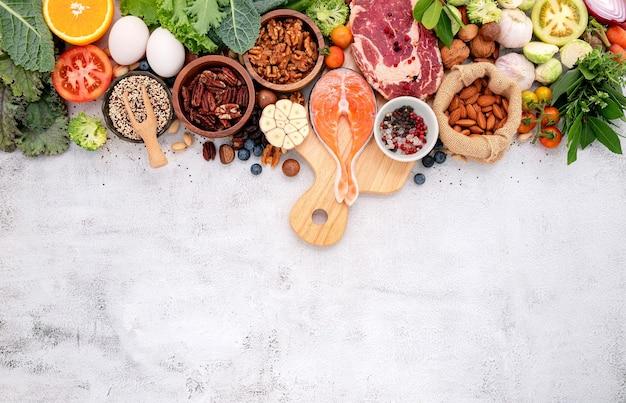Zutaten für die auswahl an gesunden lebensmitteln auf weißem betonhintergrund