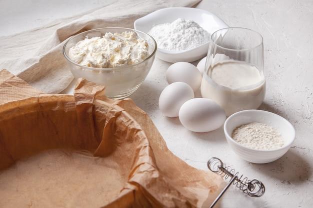 Zutaten für die herstellung von baskisch spanisch gebranntem saint sebastian käsekuchen. frischkäse, zucker, eier, mehl, sahne, auflaufform mit papier bedeckt. rezept schritt für schritt flach oben draufsicht.