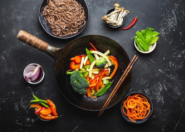 Zutaten für die herstellung von gebratenen nudeln soba. schneiden sie frisches gemüse in der wokpfanne, gekochte soba-nudeln in einer schüssel mit stäbchen zum kochen bereit, schwarzer steinhintergrund, nahaufnahme, draufsicht