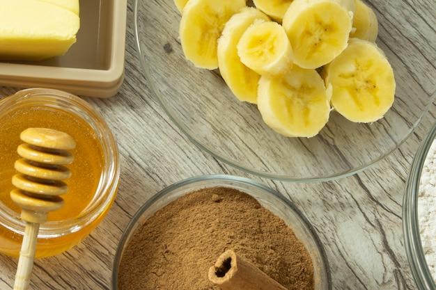 Zutaten für die herstellung von gesundem keks. banane, hafermehl, honig, zimt und butter