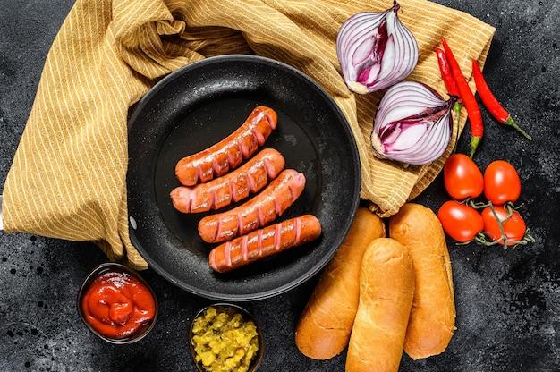 Zutaten für die herstellung von hausgemachten hot dogs. würstchen in der pfanne, frisch gebackene brötchen, senf, ketchup, gurken