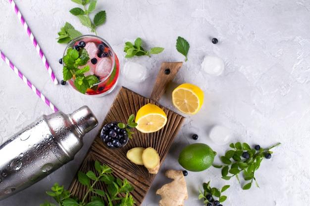Zutaten für die herstellung von limonade, mojito-cocktails oder anderen getränken mit blaubeeren auf grauem betonhintergrund