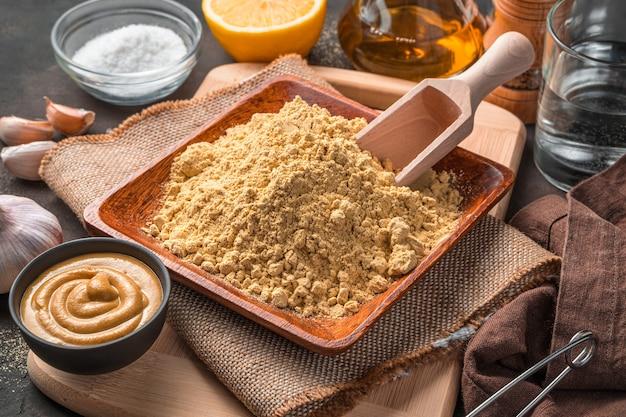 Zutaten für die herstellung von senf. senfpulver, wasser, gewürze und fertiger senf auf braunem grund. nahaufnahme, seitenansicht.