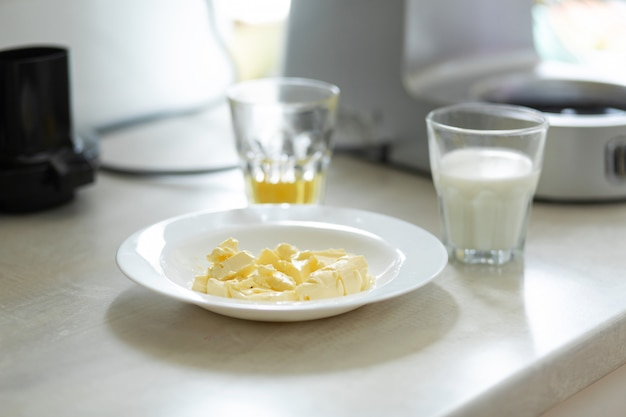 Zutaten für die herstellung von süßer sahne. butter schmilzt in einem teller