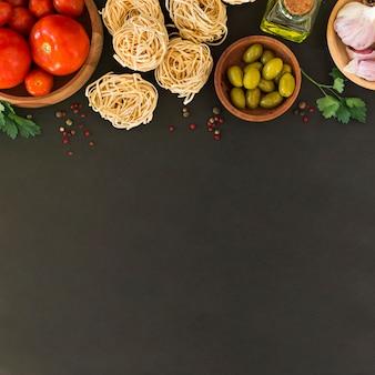 Zutaten für die herstellung von tagliatelle-teigwaren auf schwarzem hintergrund