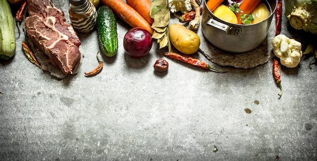 Zutaten für die suppe mit gemüse, gewürzen und fleisch. auf dem steintisch.