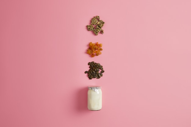Zutaten für die zubereitung eines nahrhaften schnellen snacks. joghurt, getrocknete früchte und kürbiskerne für ein köstliches bio-dessert. natürliches gesundes ernährungskonzept. frühstückszeit. leckeres essen zubereiten