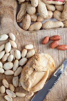 Zutaten für die zubereitung eines schnellen frühstücks mit brot und erdnüssen, erdnusspaste geröstete erdnüsse, köstliche erdnussbutter und weißbrot auf dem tisch