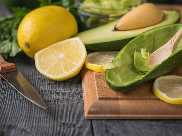 Zutaten für die zubereitung von avocadopaste auf einem schneidebrett.