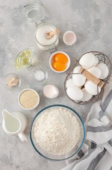 Zutaten für die zubereitung von challah-brotteig, mehl, wasser, zucker, eier, hefe, öl, salz. ansicht von oben, kopienraum.