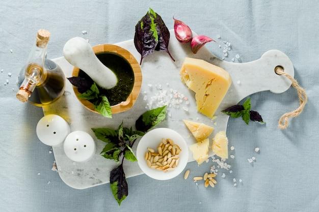 Zutaten für die zubereitung von italienischem basilikum lila pesto mit käse. auf leinenblauer tischdecke