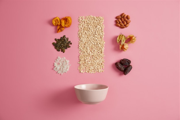 Zutaten für ein gesundes frühstück. haferflocken, getrocknete aprikosen, physalis, datteln, kürbiskerne, mandeln und kokosnüsse werden ihrem brei hinzugefügt. bio-ernährung, superfood, nährstoff-snack-konzept