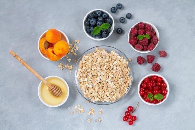 Zutaten für ein gesundes frühstück. haferflocken, honig mit schalen mit frischen sommerfrüchten und beeren: aprikose, blaubeere, himbeere, rote johannisbeere