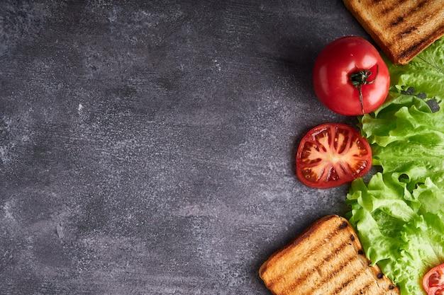 Zutaten für ein vegetarisches sandwich auf einem grauen tisch kopierraum draufsicht