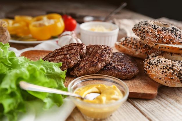 Zutaten für einen leckeren burger zu hause. brötchen, bagel, mit einem saftigen schnitzel aus rindfleisch, saucen käse frische salatblätter