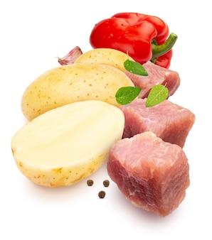 Zutaten für eintopf. würfel aus fleisch, kartoffeln, rotem pfeffer, knoblauch und gewürzen. auf weißem hintergrund isoliert.