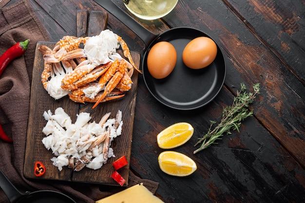 Zutaten für frühstücksomelett mit krabbenfleisch und käse, auf dunklem holzhintergrund, draufsicht flach gelegt