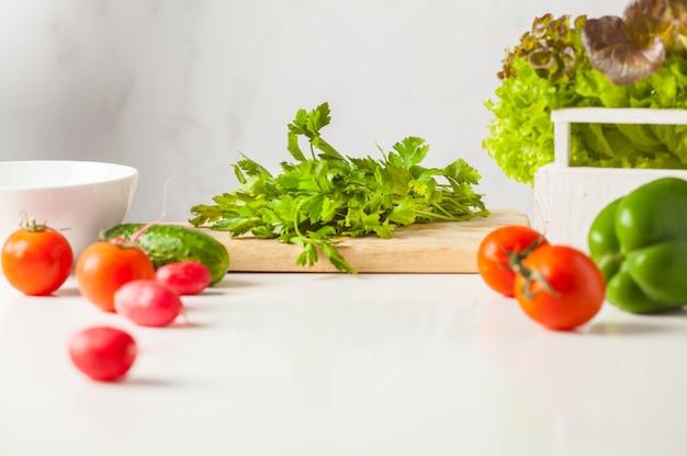 Zutaten für gemüsesalat auf einem weißen tisch, kopierraum. gesundes veganes lebensstilkonzept.