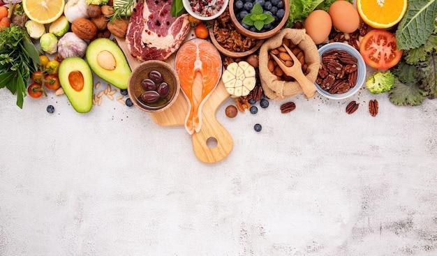 Zutaten für gesunde lebensmittelauswahl auf weißem betonhintergrund.