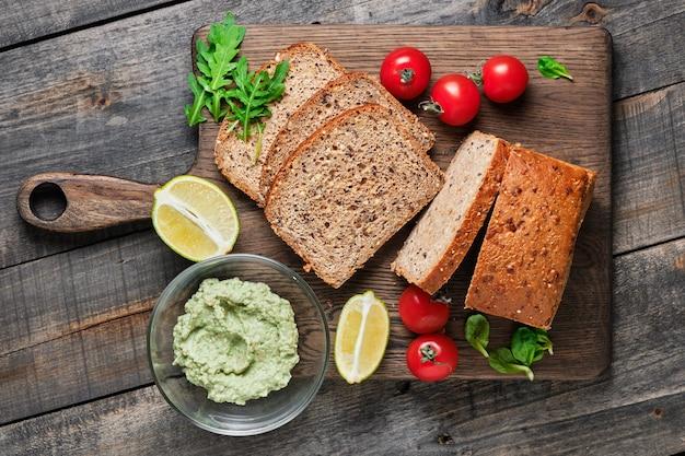 Zutaten für gesunde sandwiches. geschnittenes hausgemachtes vollkornbrot, kirschtomaten, feldsalat, rucola und avocado-guacamole.