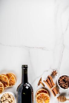 Zutaten für glühweincocktail mit weinflasche und gewürzen