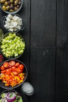 Zutaten für griechischen salat, auf schwarzem holztisch, draufsicht flach legen