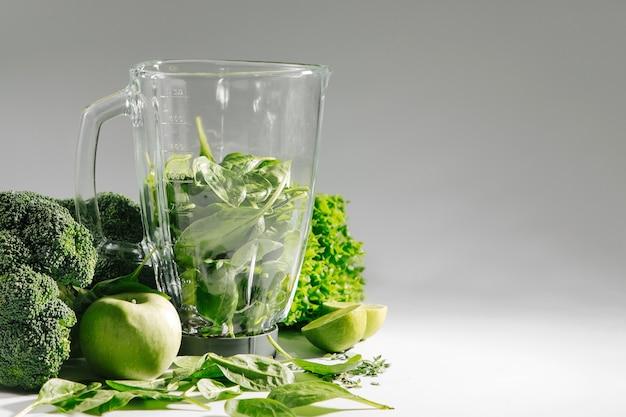 Zutaten für grüne smoothies in einem mixer. gesundes lebensmittelkonzept mit spinat und grünem gemüse. vegetarisches essen.