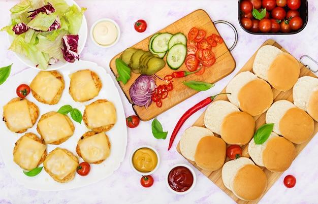 Zutaten für hamburger mit chicken burger, käse und gemüse.