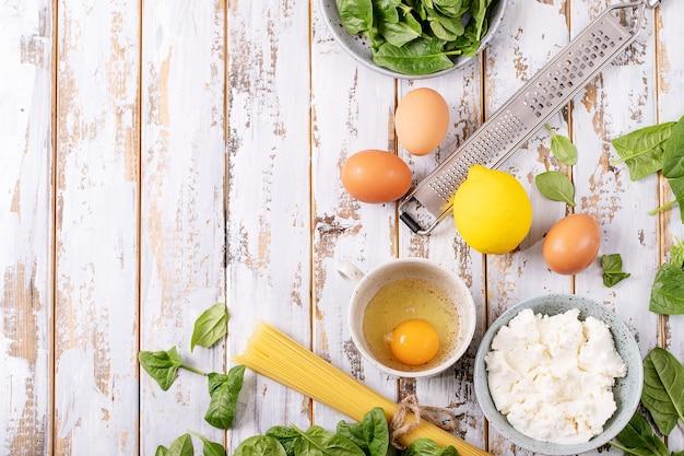 Zutaten für hausgemachte vegetarische tagliatelle-eiernudeln carbonara, serviert mit ricotta-käse, eiern und spinat über weißem holzhintergrund.