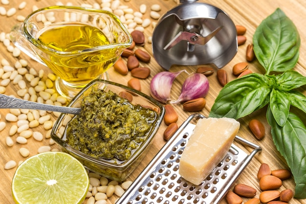 Zutaten für hausgemachtes pesto. parmesan auf reibe. pesto-sauce in glasschale. zitrone und blätter, basilikum und öl. knoblauch und pinienkerne. metallzerkleinerer. draufsicht. heller hölzerner hintergrund.