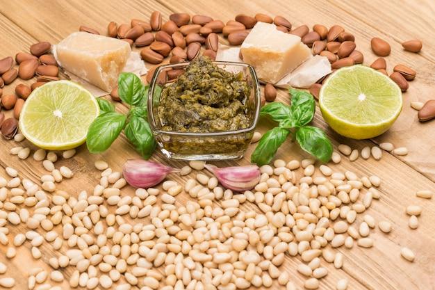 Zutaten für hausgemachtes pesto. parmesan, pesto-sauce in glasschale. zitrone und basilikum und öl. knoblauch und pinienkerne. draufsicht. heller hölzerner hintergrund.